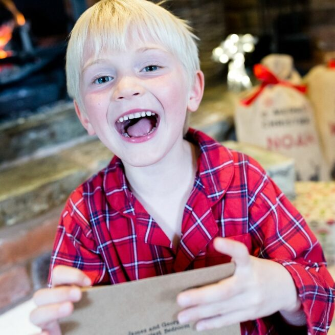 A hugely excited boy with his magiucal delivery of elfie's Christmas Advent Calendar Letters - a bundle of elf letters from International Elf Service, including a letter from santa!