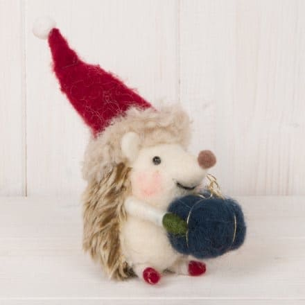 A new kind of Christmas Elf ... this totally adorable woollen Christmas decoration: a hedgehog wearing a Christmas hat and carrying a blue parcel from International Elf Service